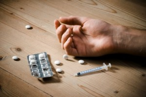 drugs next to a human hand before starting drug abuse counseling in broward county florida
