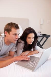 couple in front of the laptop on their bed, using online services provided by The Family Therapy Center of West Broward